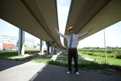 Architect with arms out standing under bridge Stock Images