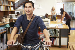 Architect Arrives At Work On Bike Pushing It Through Office royalty free stock photography