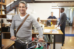 Architect Arrives At Work On Bike Pushing It Through Office. Smiling Stock Photos