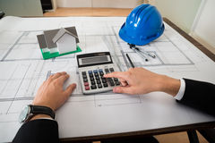 Architect With Blueprint Calculating On Calculator Stock Photography
