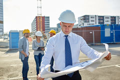 Architect with blueprint on construction site Stock Image
