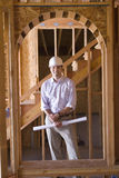 Architect with blueprint in partially built house, smiling, portrait Royalty Free Stock Photos