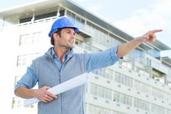 Architect with blueprint pointing away Royalty Free Stock Image