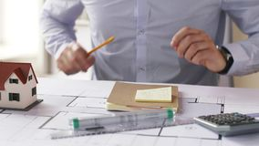 Architect with blueprint and stickers taking notes stock footage