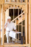 Architect with blueprint using mobile phone in partially built house Royalty Free Stock Images