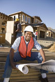 Architect With Blueprint And Workers Working In Background Stock Photography
