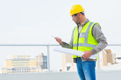 Architect with blueprints reading clipboard outdoors Royalty Free Stock Photo