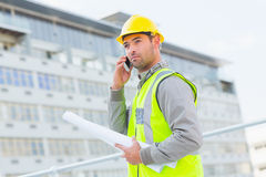 Architect with blueprints using mobile phone against building Royalty Free Stock Images