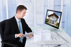 Architect browsing property on computer in office Stock Image