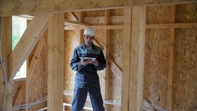 Architect or builder check plans in a half built timber frame house. Engineer on the construction of a frame wooden. House stock footage