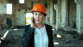 Architect builder engineer builder of ruined building looking girl work plan for the construction site construction plan. Explains in helmet construction helmet stock video
