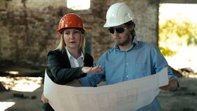 Architect builder engineer builder of ruined building looking girl work plan for the construction site construction plan. Explains in helmet construction helmet stock footage