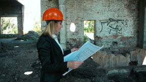 Architect builder engineer builder of ruined building looking girl work plan for the construction site construction plan. Explains in helmet construction helmet stock video footage