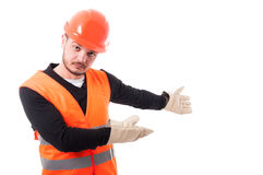 Architect or builder indicate something behind him. Architect or builder indicate something at blank copyspace behind him on white background stock images