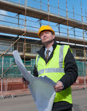 Architect on building site. Architect or engineer at work on a building site. Checking plans against the construction work. Confident gaze Stock Images