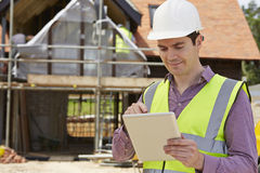 Architect On Building Site die Digitale Tablet gebruiken stock fotografie