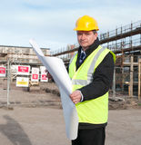 Architect on building site looks at camera. Architect or engineer at work on a building site. Checking plans against the construction work. Looking confidently Royalty Free Stock Image