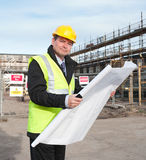 Architect on building site looks at camera. Architect or engineer at work on a building site. Holding plans for construction work. Confident gaze and smile at Stock Photography