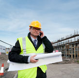 Architect on building site phoning. Architect or engineer at work on a building site. Holding plans for construction work. Confident gaze and smile at camera Stock Image