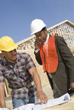Architect On Call With Co-Worker Standing With Blueprint Stock Photography