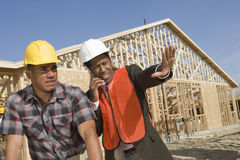 Architect On Call Gesturing Towards Site With Co-Worker Stock Images