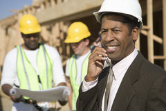 An Architect On Call With Workers In Discussion Royalty Free Stock Photos