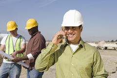 Architect On Call With Workers At Site Stock Image