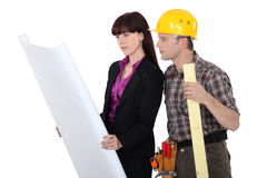 Architect and a carpenter. Looking at plans stock image