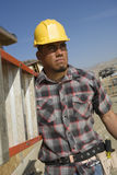 Architect Carrying Stepladder At Site. Manual worker carrying stepladder at construction site Royalty Free Stock Photo