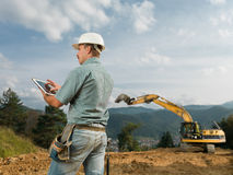 Architect checking construction progress. Back view of caucasian engineer standing on construction site browsing on digital tablet Stock Photography