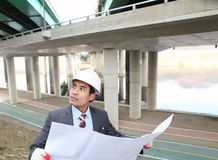 Architect checking a drawing. Architect checking a plan with highway on the background Royalty Free Stock Photos