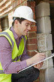 Architect Checking Insulation During Construction Project. Architect With Clipboard Checking Insulation During Construction Project Stock Photo