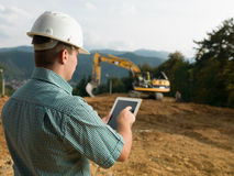 Architect checking plan on tablet. Back view of caucasian engineer standing on construction site checking plan on digital tablet Stock Image