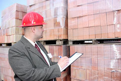 An architect with checklist. An architect with helmet filling in a checklist in front of pallets of bricks Stock Photos