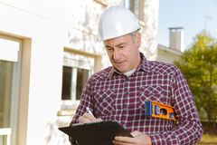 Architect with clipboard in hardhat at construction site stock images