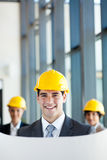 Architect and co-workers. Modern young male architect and co-workers in office Royalty Free Stock Image