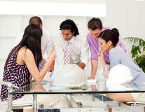 Architect co-workers reviewing blueprints stock image
