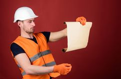 Architect concept. Man in helmet, hard hat holds building plan, controls works, red background. Engineer, architect. Builder on strict face holds old blueprint Royalty Free Stock Images