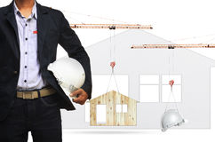 Architect and construction crane lifting home and safety helmet Royalty Free Stock Photography