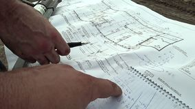 An architect and a construction engineer check the building plan of the building, compare the exact dimensions of the stock video