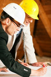Architect and construction engineer discussing. Architect and construction engineer or surveyor discussion plans and blueprints. Both are wearing hardhats and Royalty Free Stock Images