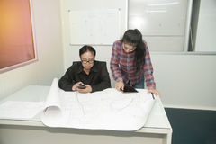 Architect and construction engineer discussing plan in office. Stock Photos