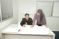 Architect and construction engineer discussing plan in office. Royalty Free Stock Images