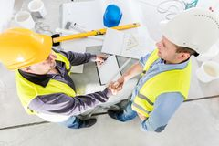 Architect and construction engineer handshake. Successful building experts meeting. Real estate market. Top view Stock Photos