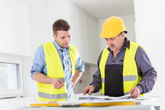 Architect and construction engineer indoor meeting. Stock Photos