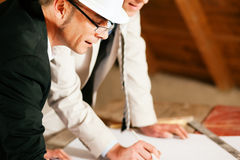 Architect and construction engineer with plan. Architect and construction engineer or surveyor discussion plans and blueprints. Both are wearing hardhats and are Stock Photography