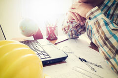 Architect with construction plan. On office desk under shinning light Stock Photography
