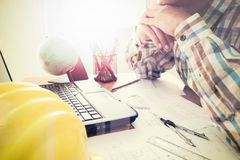 Architect with construction plan in office. Architect with construction plan on office desk under shinning light. Horizontal, film effect Stock Image