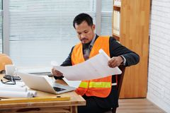 Architect with construction plan. Portrait of Filipino architect examining construction plan Stock Photography