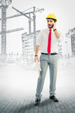 Architect at construction site. With cellphone and blueprints Stock Photo